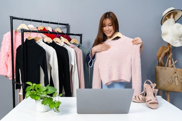 Junge frau, die kleidung und accessoires online durch laptop-live-streaming, geschäft online e-commerce zu hause verkauft