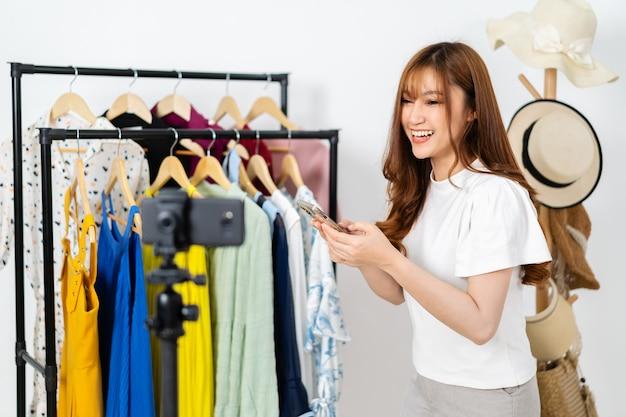 Junge frau, die kleidung und accessoires online per smartphone-live-streaming, online-e-commerce für unternehmen zu hause verkauft