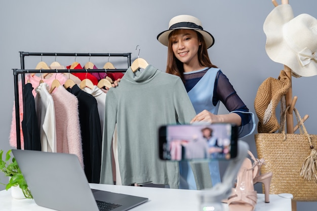 Junge frau, die kleidung und hut online durch smartphone-live-streaming, online-geschäfts-e-commerce zu hause verkauft