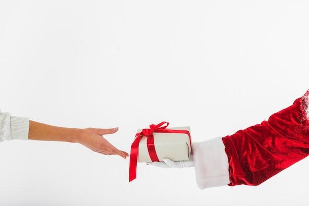 Junge frau, die kleine geschenkbox bei santa claus nimmt