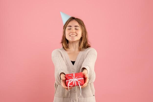 Junge frau, die kleine weihnachtsgeschenke auf rosa hält