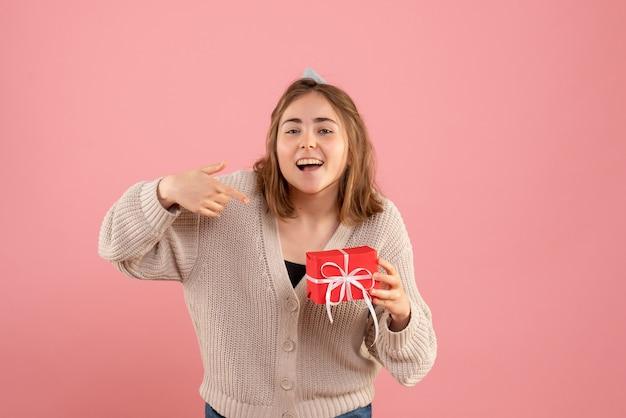 Junge frau, die kleine weihnachtsgeschenke auf rosa hält Kostenlose Fotos
