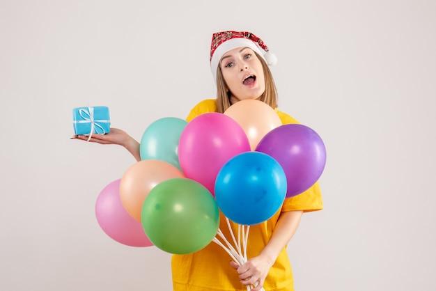 Junge frau, die kleines geschenk und bunte luftballons auf weiß hält