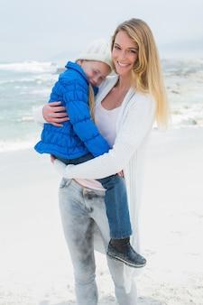 Junge frau, die kleines mädchen am strand trägt