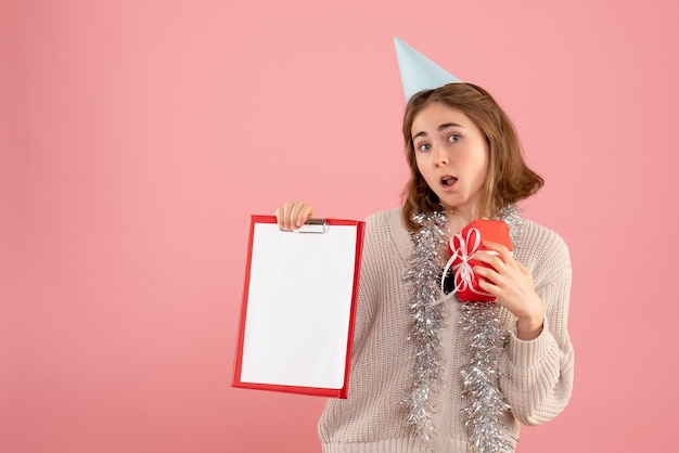 Junge frau, die kleines weihnachtsgeschenk und notiz auf rosa hält