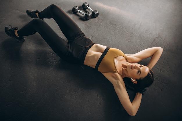 Junge frau, die knirschen auf boden im fitnessstudio tut