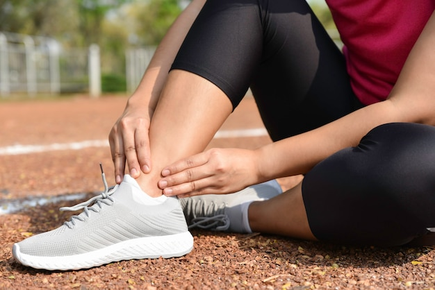 Junge frau, die knöchel in den schmerz auf der stadionsbahn hält. gebrochene twisted joint running sportverletzung.