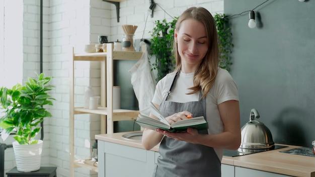 Junge frau, die kochbuch in der küche liest und rezept sucht