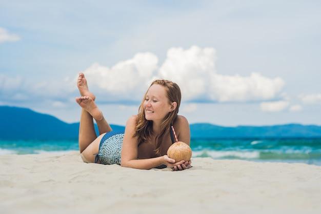 Junge frau, die kokosmilch am strand trinkt