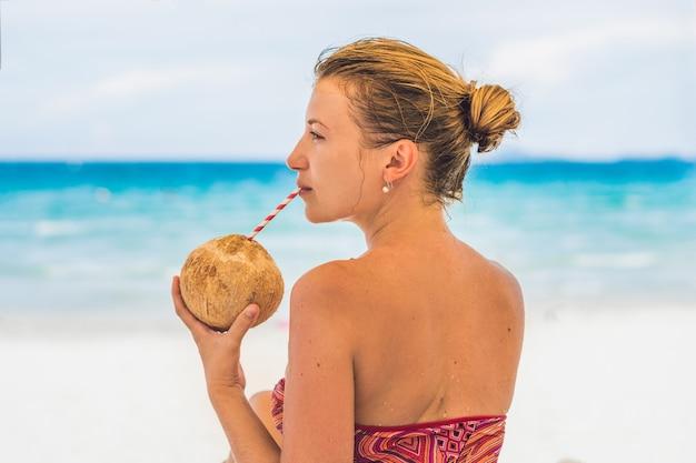 Junge frau, die kokosmilch auf chaiselongue am strand trinkt