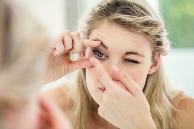 Junge frau, die kontaktlinse anwendet