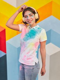Junge frau, die kopfhörer in festivalfarben trägt
