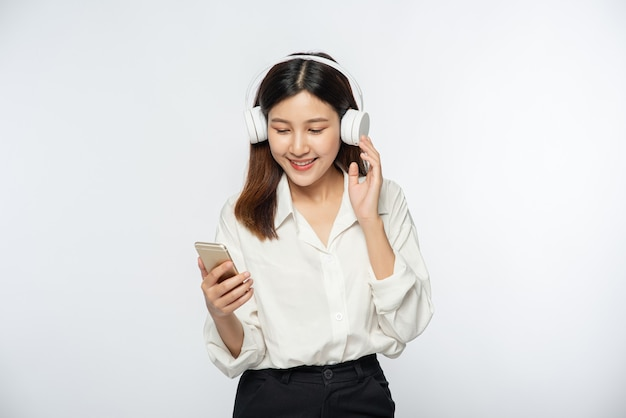 Junge frau, die kopfhörer trägt und musik auf einem smartphone hört