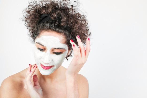 Junge frau, die kosmetische creme auf ihrem gesicht gegen weißen hintergrund aufträgt