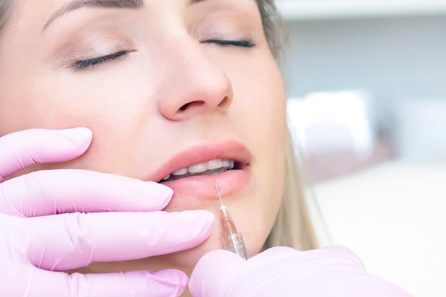 Junge frau, die kosmetische injektion erhält. frau in einem schönheitssalon. klinik für plastische chirurgie.