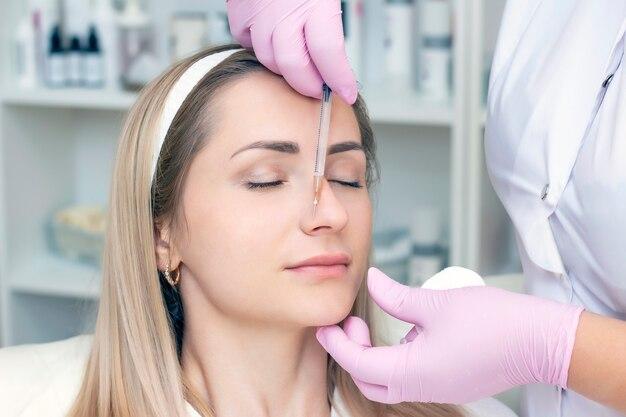 Junge frau, die kosmetische injektion von botox, nahaufnahme erhält