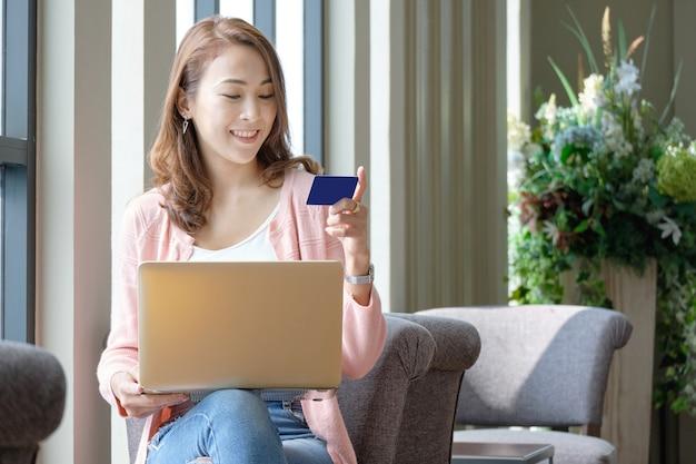 Junge frau, die kreditkarte für online kaufen bei der anwendung von laptops in lächelnder stimmung hält.