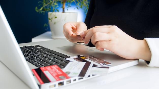 Junge frau, die kreditkarte für online-shopping auf laptop von zu hause aus wählt. konzept des online-shoppings und des e-commerce.