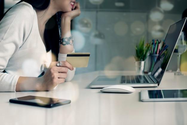 Junge frau, die kreditkarte hält und laptop-computer verwendet. online-shopping-konzept.