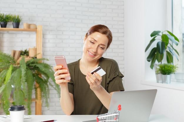 Junge frau, die kreditkarte hält und laptop-computer verwendet. online-shopping-konzept