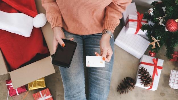 Junge frau, die kreditkarte hält und online kaufen tut.
