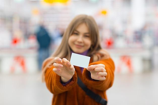 Junge frau, die kreditkarte in händen hält