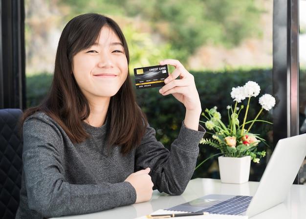 Junge frau, die kreditkarte mit laptop-computer auf plattform hält