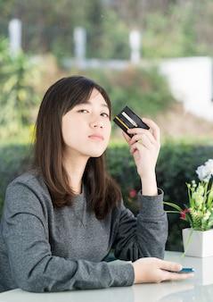 Junge frau, die kreditkarte zeigt und smartphone für online-einkauf, online-einkaufskonzept hält