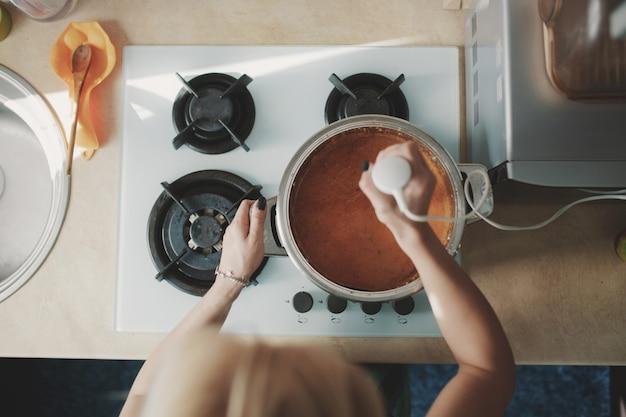 Junge frau, die kürbissuppe zubereitet