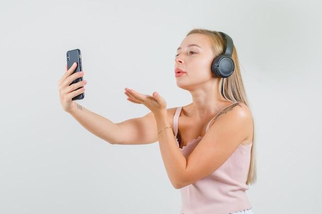Junge frau, die kuss auf videoanruf im unterhemd sendet
