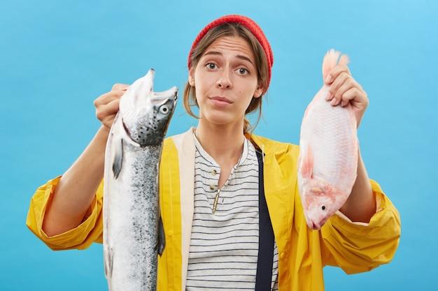 Junge frau, die lässig gekleidet ist und zwei fische in den händen hält