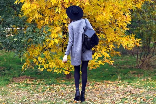Junge frau, die lässiges elegantes straßenart-outfit, hut und mantel trägt, die im herbsttag-stadtpark gehen und zurückwerfen.