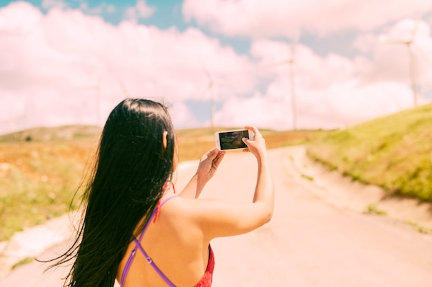 Junge frau, die landschaft am telefon fotografiert