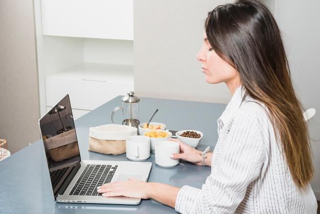 Junge frau, die laptop am frühstückstische verwendet