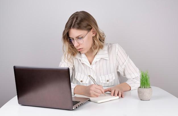 Junge frau, die laptop benutzt und etwas in ein notizbuch schreibt