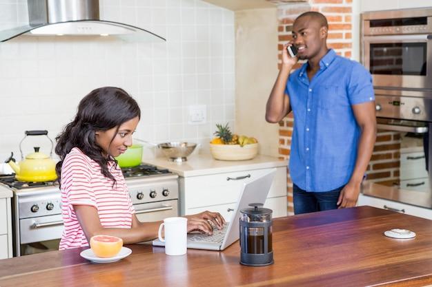Junge frau, die laptop in der küche verwendet