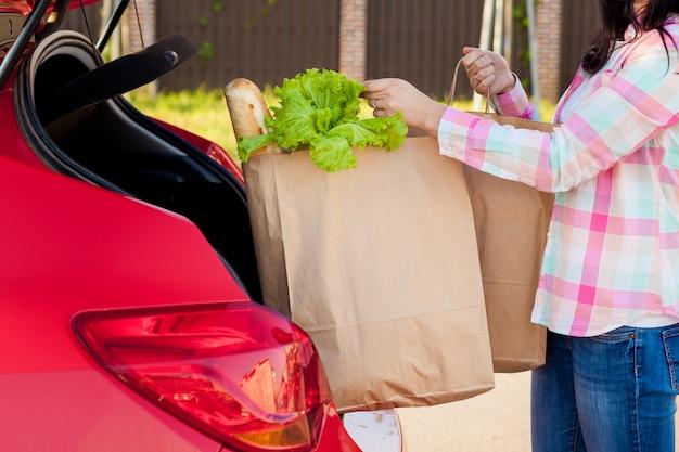 Junge frau, die lebensmittel aus einem supermarkt in papiertüten in den kofferraum eines autos legt