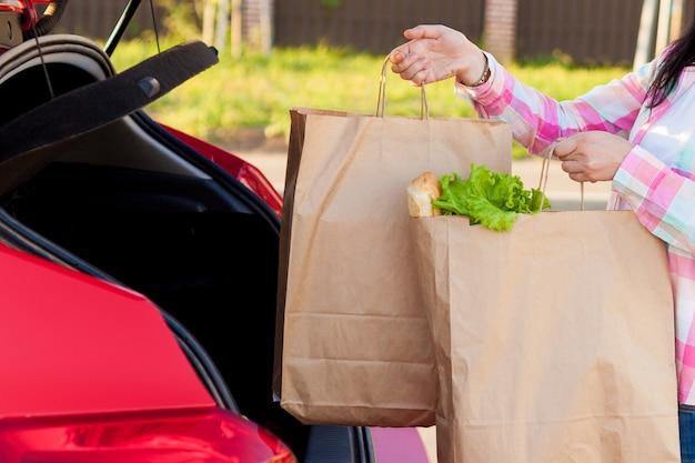 Junge frau, die lebensmittelgeschäfte von einem supermarkt in papiertüten in den kofferraum eines autos einsetzt.