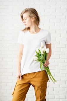 Junge frau, die leere weiße t-shirt hält tulpenblumen, die gegen die weiße backsteinmauer aufwerfen