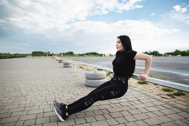 Junge frau, die liegestütze auf horizontaler stange im freien tut. frauentraining nahe dem stadion. fitness-, sport-, trainings- und lifestyle-konzept.