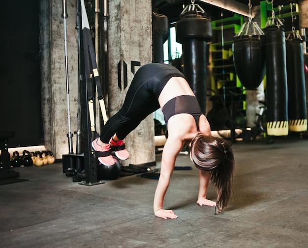 Junge frau, die liegestütze tut, während beine an trx im fitnessstudio hängen.