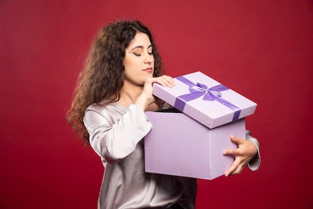 Junge frau, die lila geschenkbox prüft.
