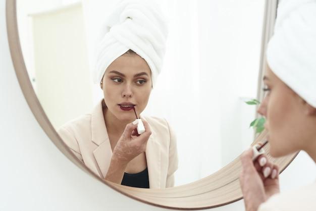 Junge frau, die lippenstift anwendet