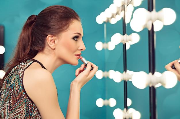 Junge frau, die lippenstift vor einem spiegel anwendet