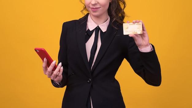 Junge frau, die lokalisiert über gelbem wandhintergrund unter verwendung des mobiltelefons hält, das debitkarte hält.