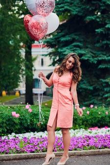 Junge frau, die luftballons am park hält