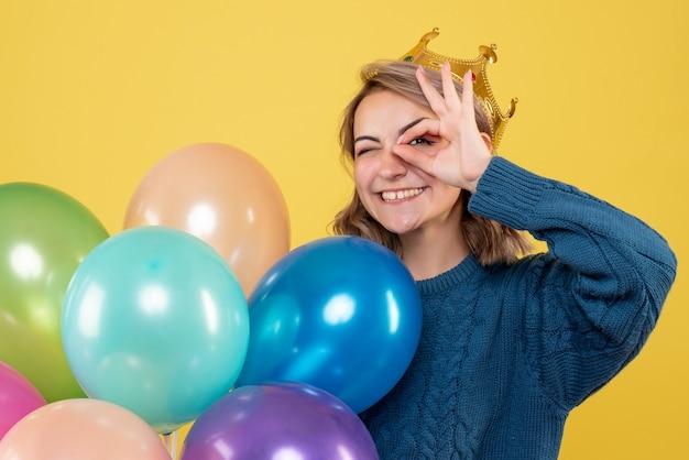 Junge frau, die luftballons in der krone auf gelb hält