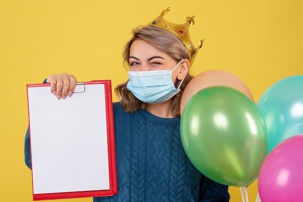 Junge frau, die luftballons in der sterilen maske auf gelb hält
