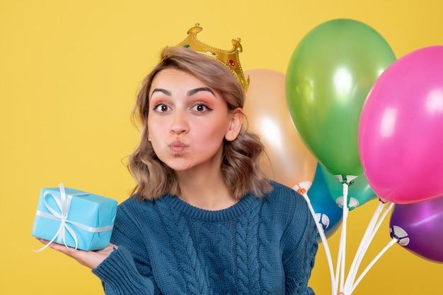 Junge frau, die luftballons und wenig geschenk auf gelb hält