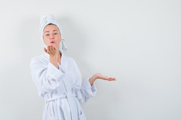 Junge frau, die luftkuss mit schmollenden lippen bläst, handfläche beiseite in weißem bademantel, handtuch und niedlich aussehend. vorderansicht.